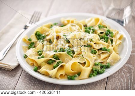 Tagliatelle Pasta With Cream And Peas On A Plate.