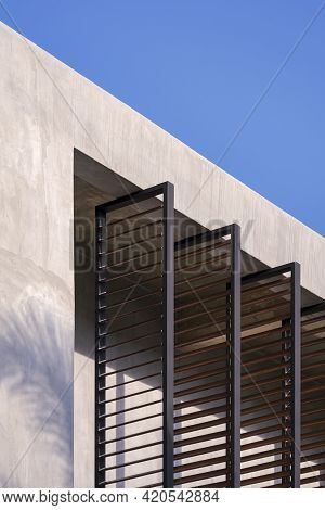 Low Angle View Of Folding Metal Sunshade Battens On Concrete Wall Of House Building In Loft Style Ag