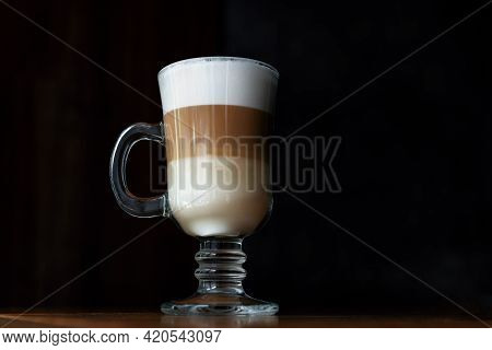 Three-layer Latte On A Dark Background. Coffee Latte In A Glass Cup With Black Background. Layering.