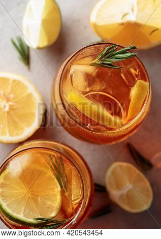 Iced Tea With Lemon, Lime And Ice Garnished With Rosemary Twigs. Frozen Glasses With Citrus Slices.