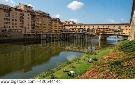 Florence, Italy - October 6 2017: People Resting At The Riverside And Ponte Vecchio Landmark Reflect