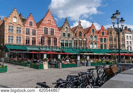 People Enjoy A Day Out In The Restaurants On Market Square In Bruges With Many Historic Brick Buildi