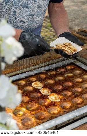 A Vertical View Of A Male Baker Preparing Fresh The Sweet Dutch Batter Treat Called Poffertjes On A