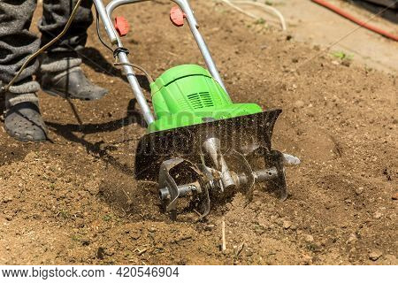 Gardening. Spring Work On The Farm. Land Cultivation With An Electric Cultivator. Man Plows The Eart