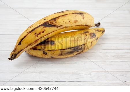Plantain Or Green Banana (musa X Paradisiaca) On White Wooden Background