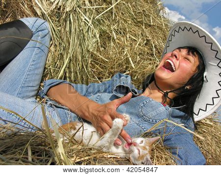 cheerful cowgirl playing with funny kitten in the ranch poster