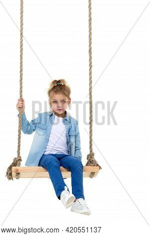 Lovely Blonde Girl Swinging On Rope Swing And Looking At Camera