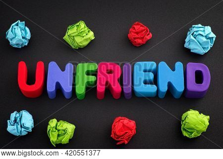 The Word Unfriend Made Out Of Polymer Clay Letters With Some Colorful Crumpled Paper Balls Around It