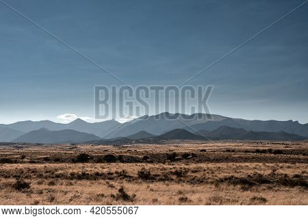 Dry Grass Across Brown Field Below Mountains In Nevada's Great Basin National Park