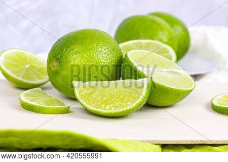 Fresh Green Juicy Limes And Lime Slices In The Kitchen On Light Background.