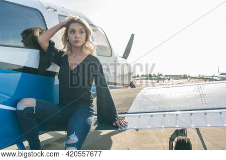 A gorgeous young blonde model poses outdoors with a single engine aircraft at a local airport