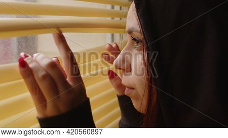 Close Up Of Young Woman Watching Through Window Blinds At Home. Portrait Of Curious Female Observing