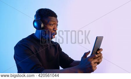 Guy Wearing Headphones And Holding A Tablet Watching Some Video. Intense Expressions On His Face. Bl