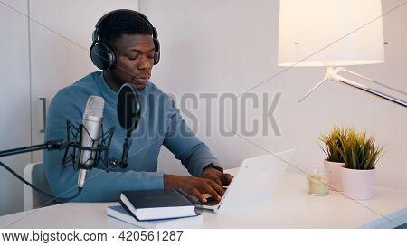 Man Wearing Headphones Doing An Online Meeting Using A Laptop And Microphone. Concept Of Online Meet