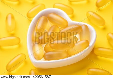 Close Up Omega 3 Capsules In A Heart-shaped Plate On Yellow Background. Fish Oil Softgels. Concept O