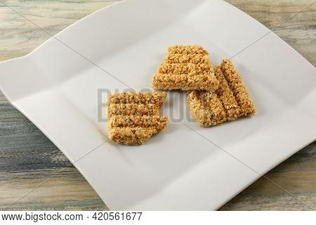 Pieces Of Broken Sugar Glazed Sesame Brittle Bar On White Snack Plate