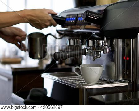 A White Ceramic Cup Placed On The Coffee Maker. Prepare For Making Espresso Coffee. Barista Holding