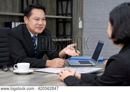 Asian Manager In The Black Suit Interviewed The Applicant With A Smile. The Atmosphere Of Job Interv