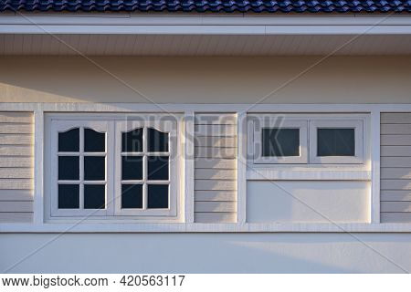 Soft Sunlight On Surface Of White Wooden Windows On Cement Wall Of Beige House With Blue Ceramic Til