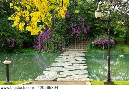 Grey Stepping Stone Curve Concrete Bridge And Walkway Cross A Small Lake Among Greenery Trees, Flowe