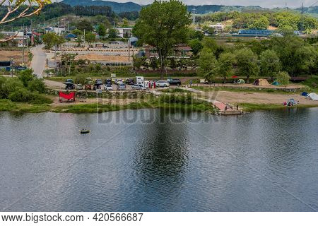 Daejeon, South Korea; May 2, 2021: Landscape Of River And Camping Site With Trees, Mountains Under C