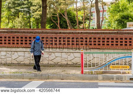 Daejeon, South Korea; May 2, 2021: Unidentified Man In Blue Cap Spraying Insecticide On Plants In Si