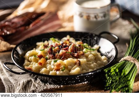 Halusky As Traditional Slovak Potato Gnocchi With Sheep Cheese Bryndza, Fried Bacon And Chives.
