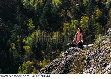 Attractive Woman Doing Yoga. Healthy Lifestyle. Woman Doing Yoga In The Mountains. Girl Doing Yoga A