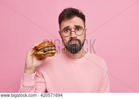 Unhappy Bearded Hungry European Man Gets High Calories Snack Holds Appetizing Hamburger Eats Unhealt