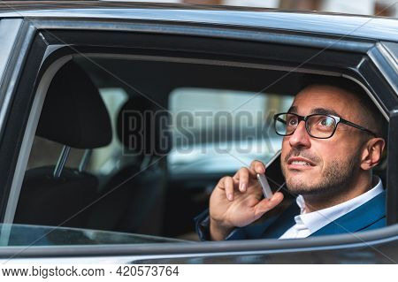 Businessman In The Back Seat Of A Taxi Having Phone Call.