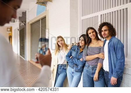 Multi-ethnic Group Of Friends Taking Photos With A Smartphone In The Street.