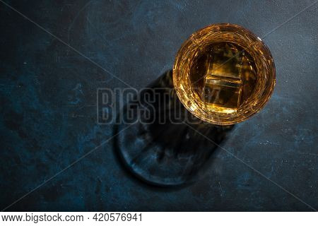 Whiskey, Scotch Or Bourbon Glass With Ice On Blue  Background With Hard Lights And Shadows, Top View