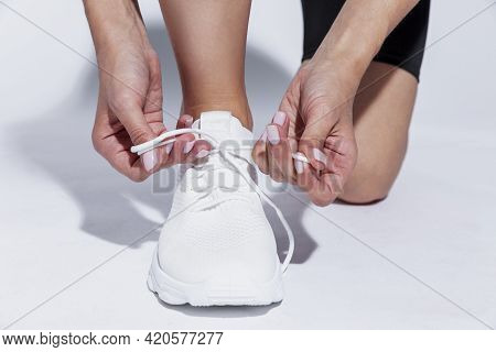 The Sportswoman Is Tying The Laces On The Shoes. Close-up. Hard Sunlight, White Background.