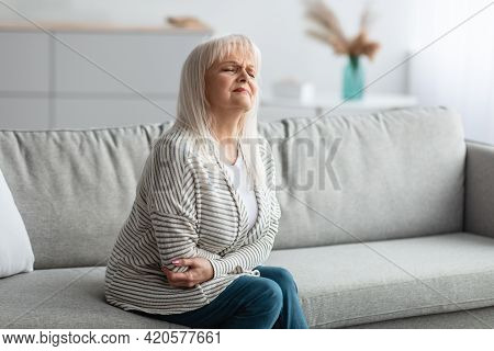 Mature Woman Suffering From Stomachache, Touching Her Tummy