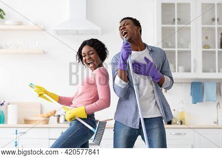 Ecstatic Black Couple Imitating Rock Stars While Cleaning House