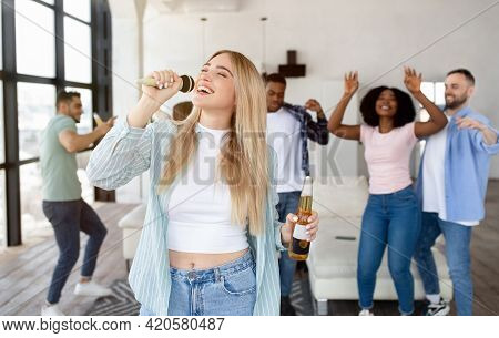 Pretty Young Blonde Lady Singing Karaoke At Home, Holding Bottle Of Beer, Dancing And Having Fun Wit