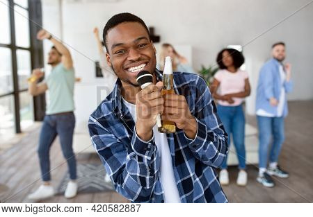 Happy Black Guy Holding Bottle Of Beer And Microphone, Performing Song, Singing Karaoke On Party Wit