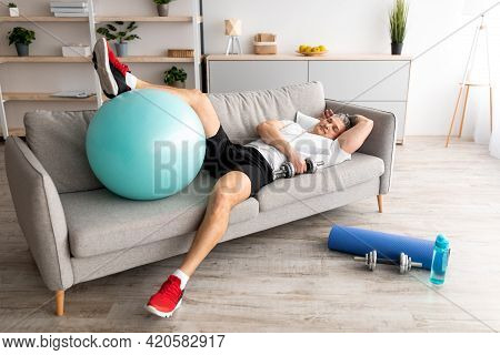 Fatigue Mature Man Resting On Sofa After Active Hard Training. Tired Sportsman With Dumbbells And Fi