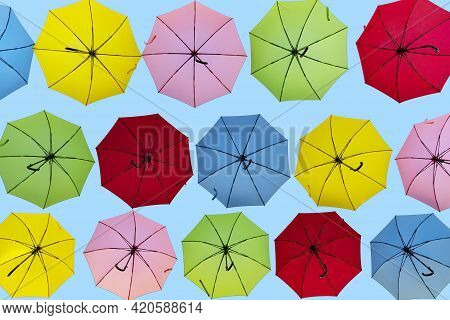 Rows Of Red, Pink, Yellow,green And Blue Umbrellas On A Light Blue Background.