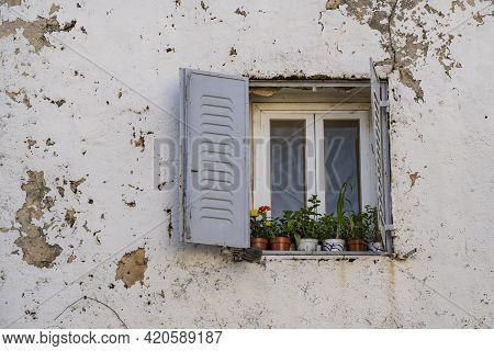 Flower Pots Decorating A Window In An Old, Decrepit House, Typical Of Old Jerusalem.