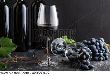 Wine Glass With Red Wine. Red Wine Bottles, Grape Bunches With Leaves And Vines On Dark Rustic Concr
