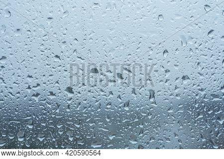 Raindrops On The Transparent Window Pane In Rainy Weather.