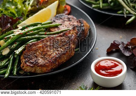 Grilled Pork Loin Chops Served With French Green Beans Salad And Beer