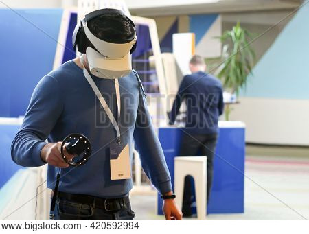 The Person At The Exhibition Tries Virtual Reality In 3d Glasses, Headphones And A Remote Control