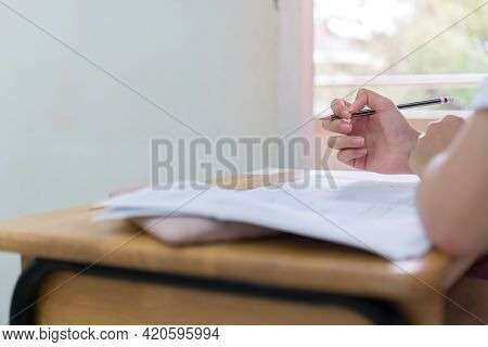Hand Female Asian Student Reading Document Exercise And Taking Exam Test At Classroom In High School