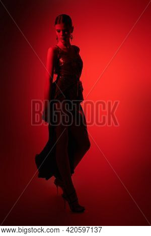 Graceful young woman dancer poses in elegant long dress and high heels. Studio portrait in red light.