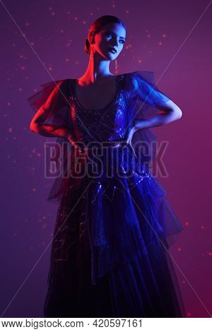 Evening fashion. Beautiful graceful girl poses in a luxury evening dress in mixed colored light. Studio portrait.