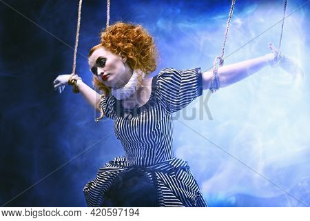 Circus and puppet theater. The actress plays a doll on strings at a performance in a puppet theater. A portrait in retro style.
