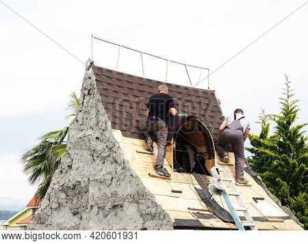 Two Roofers Covering The Roof Of A Decorative Clay House In A Park Among Green Southern Trees Agains