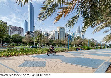 Abu Dhabi, Uae - April 30, 2021: Man Riding Bike On Abu Dhabi Corniche In The Morning With Modern Ci